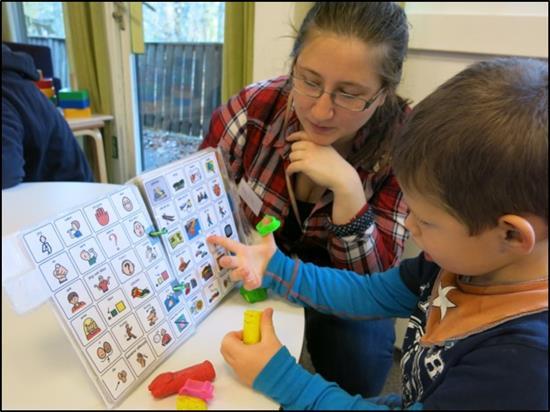 Bildet viser en gutt som kommuniserer med symboler