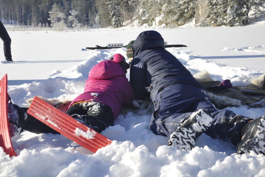 En jente og gutt ligger på magen i snøen og skyter på blink