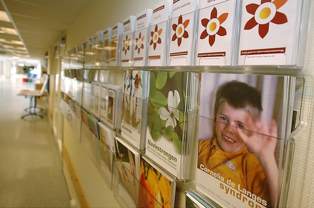 Foto av en vegg full av brosjyrer fra Frambu
