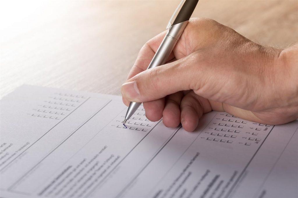 Bildet viser en hånd som skriver i et skjema