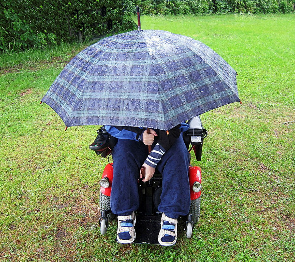 Ungdom med fremadskridende sykdom under en stor paraply