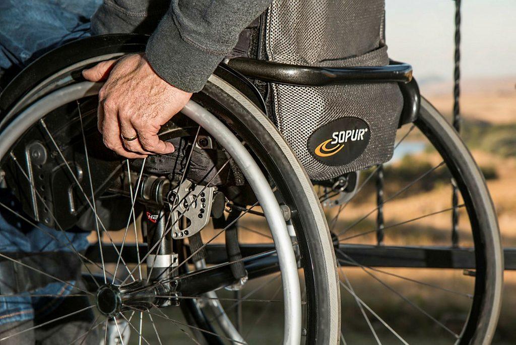 Mann i manuell rullestol