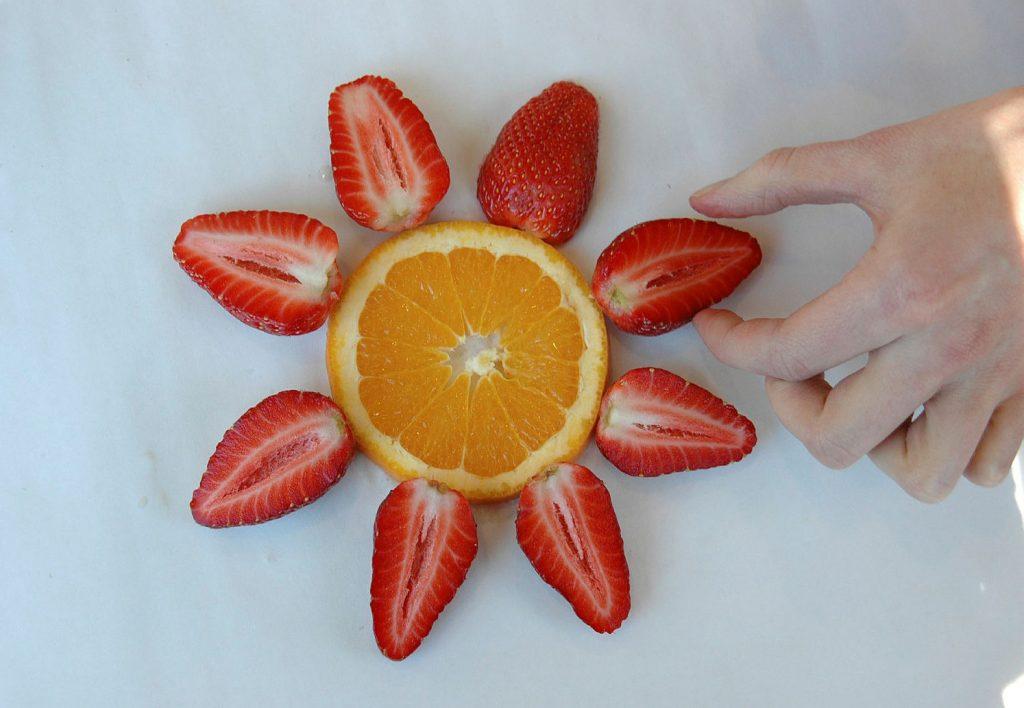 Hånd som tar etter frukt fra et fat med oppskåret frukt