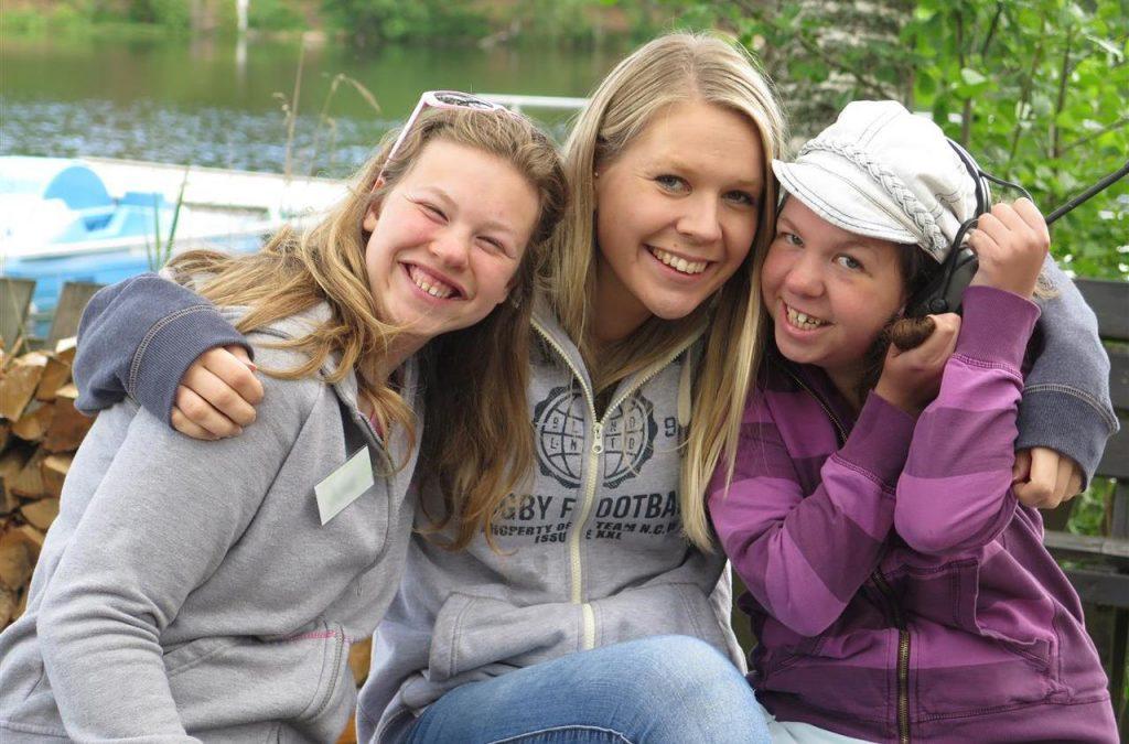 Tre unge jenter holder rundt hverandre