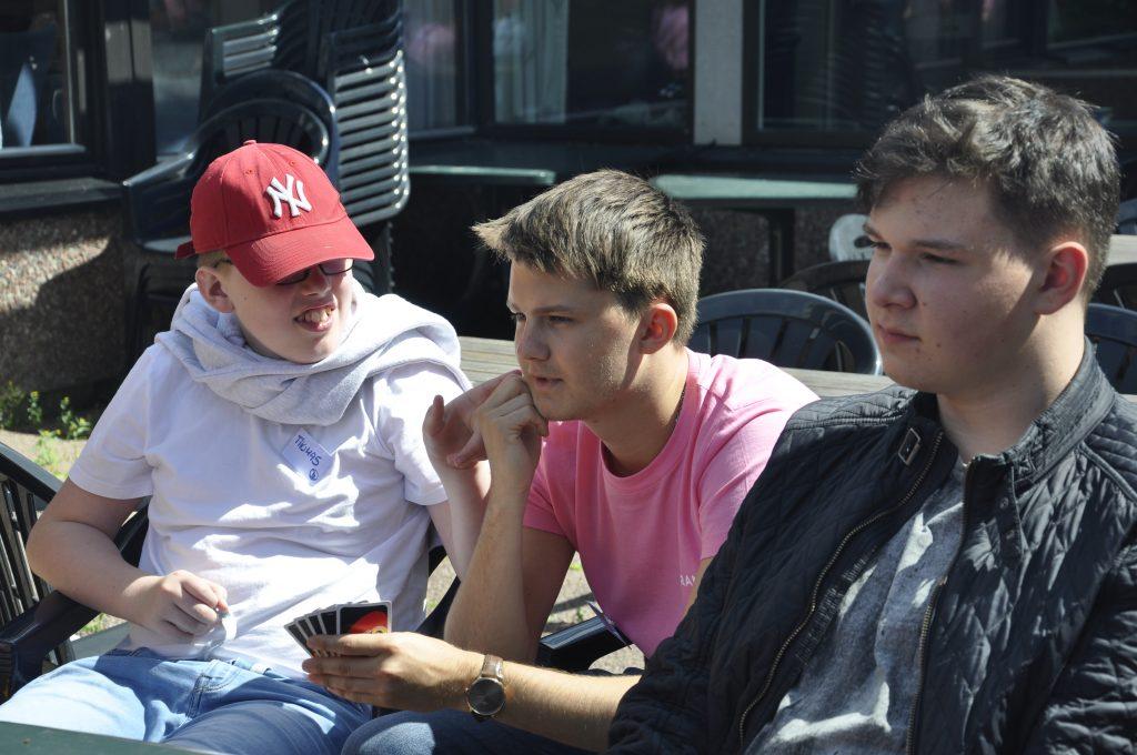 Tre personer sitter ute i atriet på Frambu