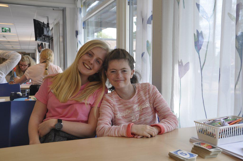 To personer sitter og smiler til kamera