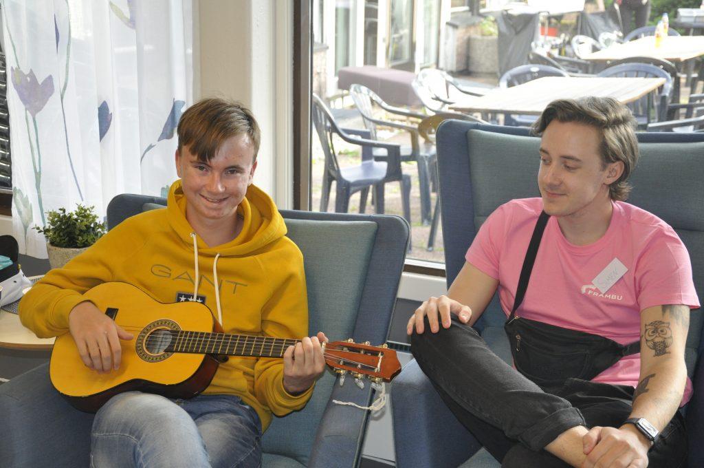 Tp personer sitter og en har gitar