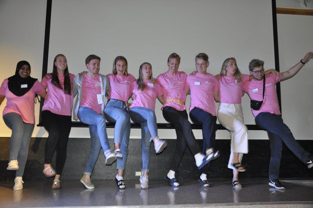 Leirhjelperne danser sammen på scenen med rosa t-skjorter