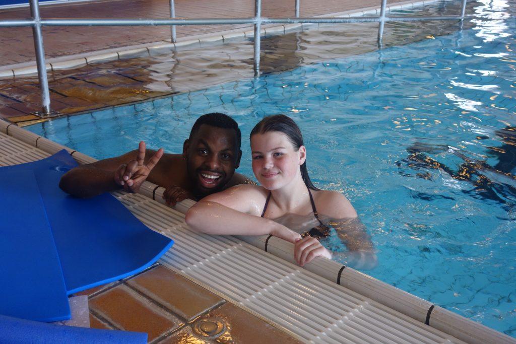 To personer i vannet ved bassengkanten