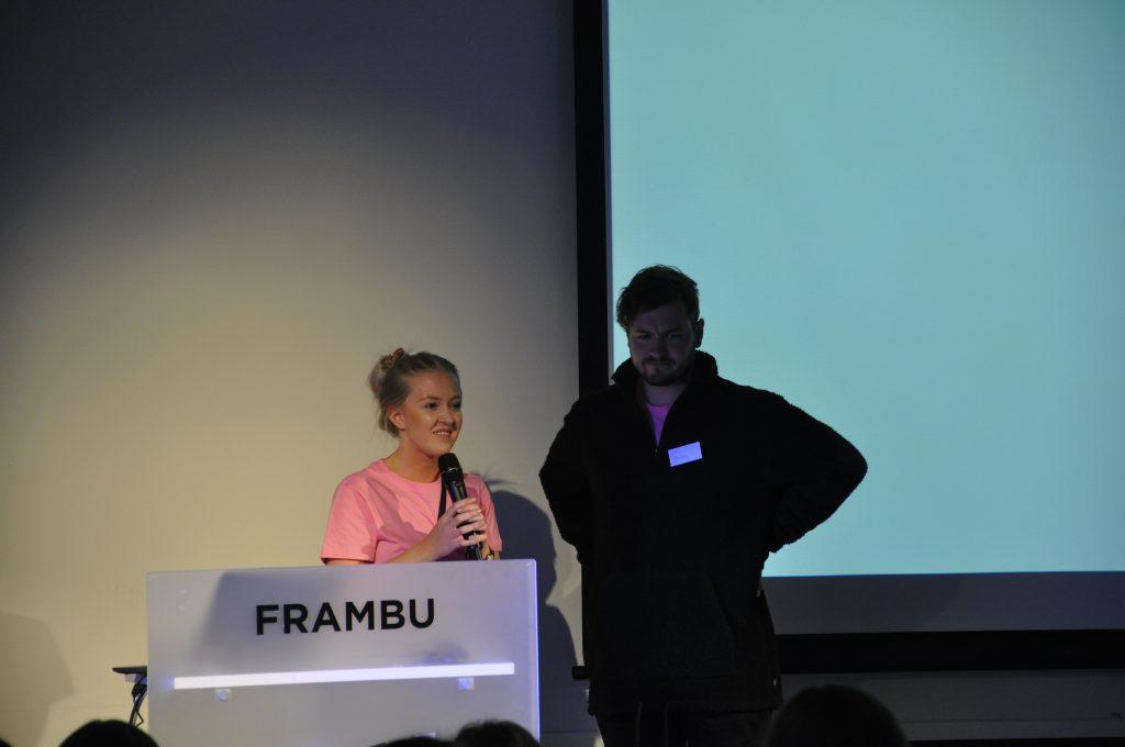 To leirhjelpere snakker i mikrofon på scenen