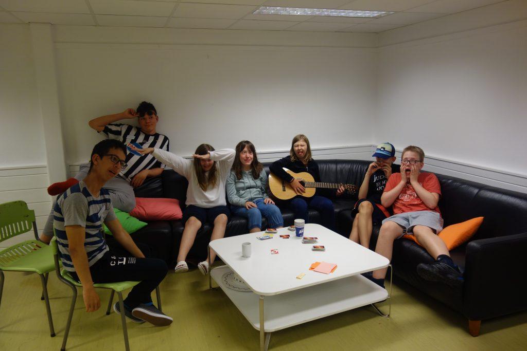 En gruppe deltakere sitter i sofa med gitar