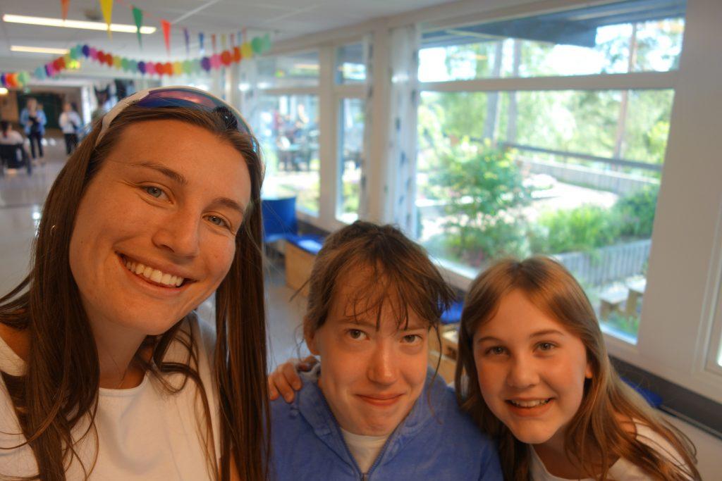 Tre personer smiler til kamera i gangen på Frambu