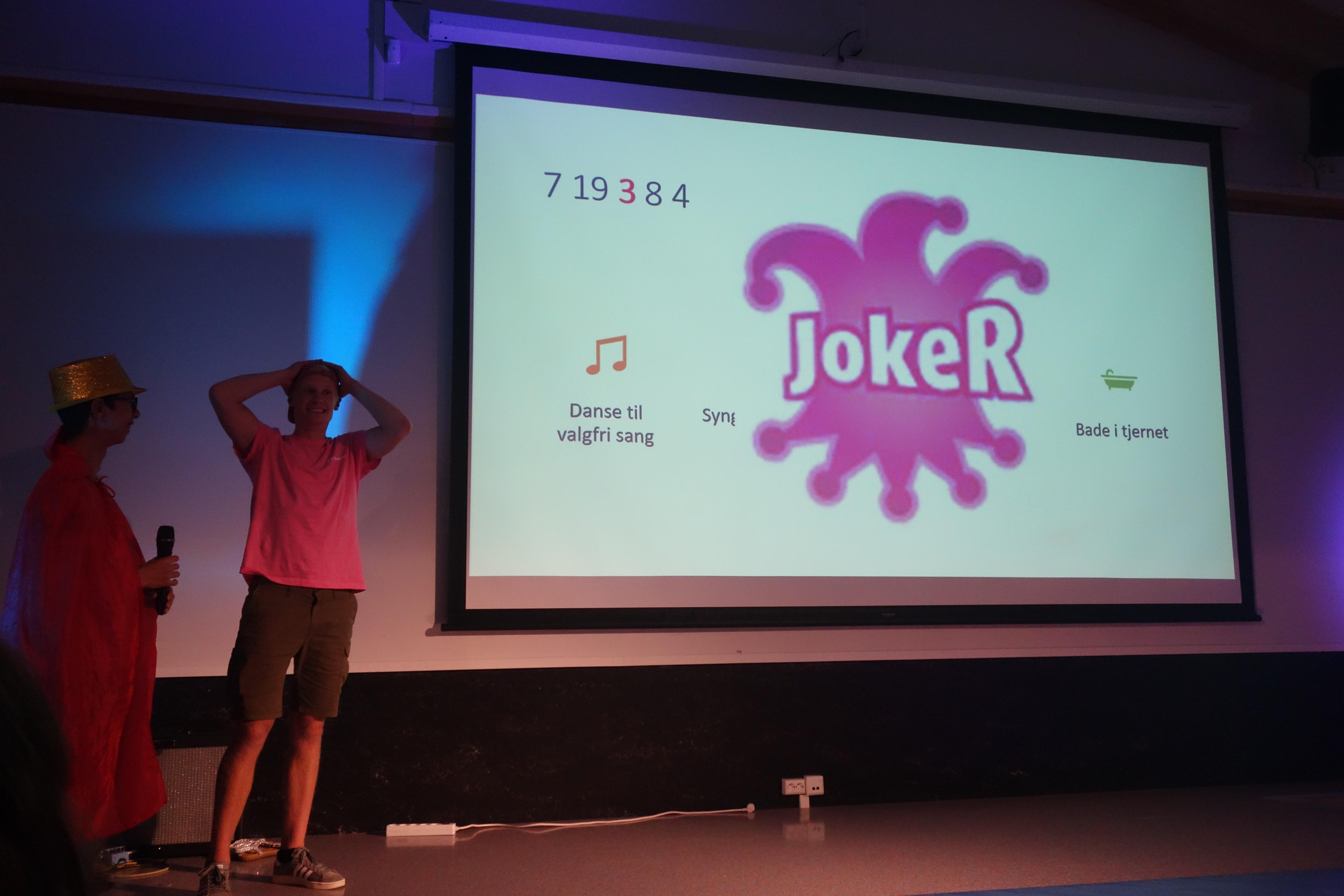 """To personer på scenen foran en powerpoint hvor det står """"joker"""""""