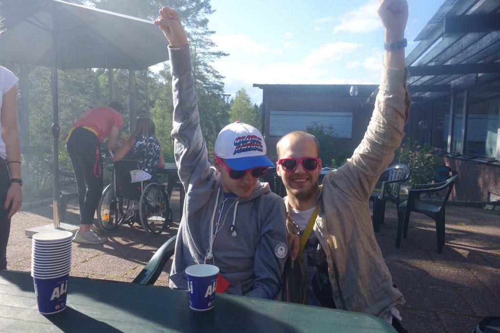 To personer hever hendene over hodet ute i atriet