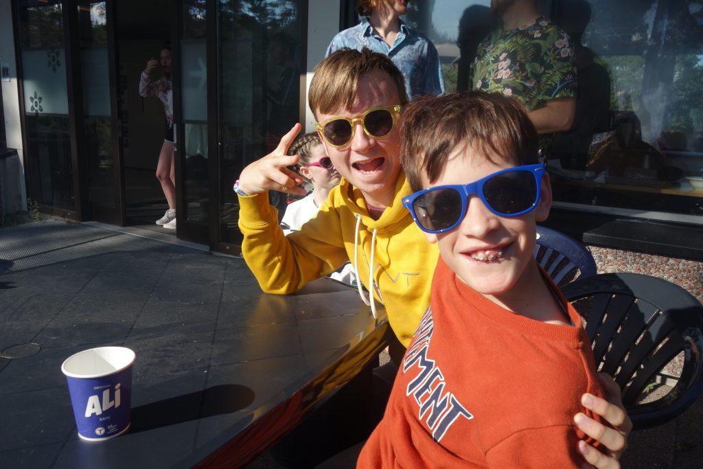 To personer sitter med kule solbriller å ute