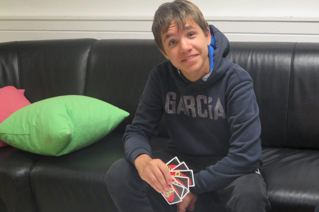 En person sitter i sofa med kort