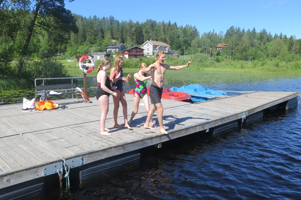 Fire personer i ferd med å hoppe fra brygga og ut i vannet