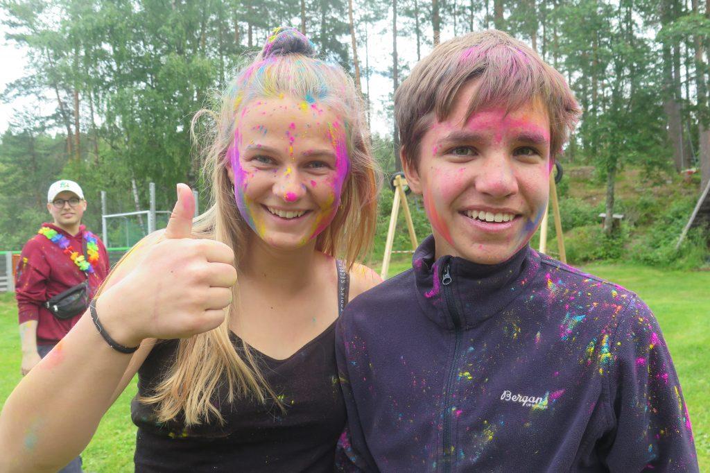 To personer med farger i ansiktet smiler til kamera