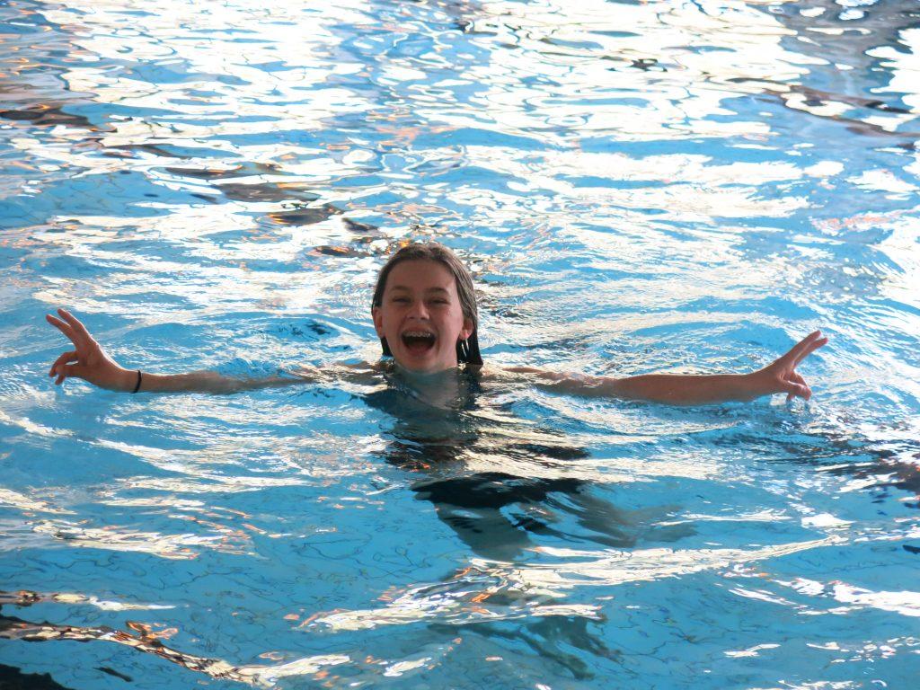 Person smiler i bassenget