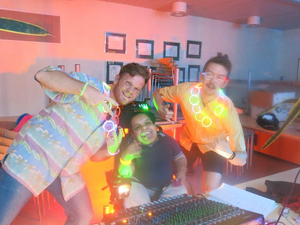 Tre personer kjører disco ved miksebordet