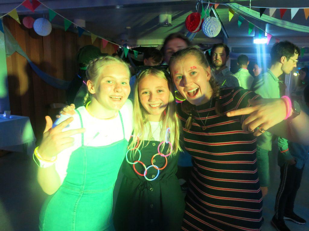 Tre personer poserer foran kamera på disco