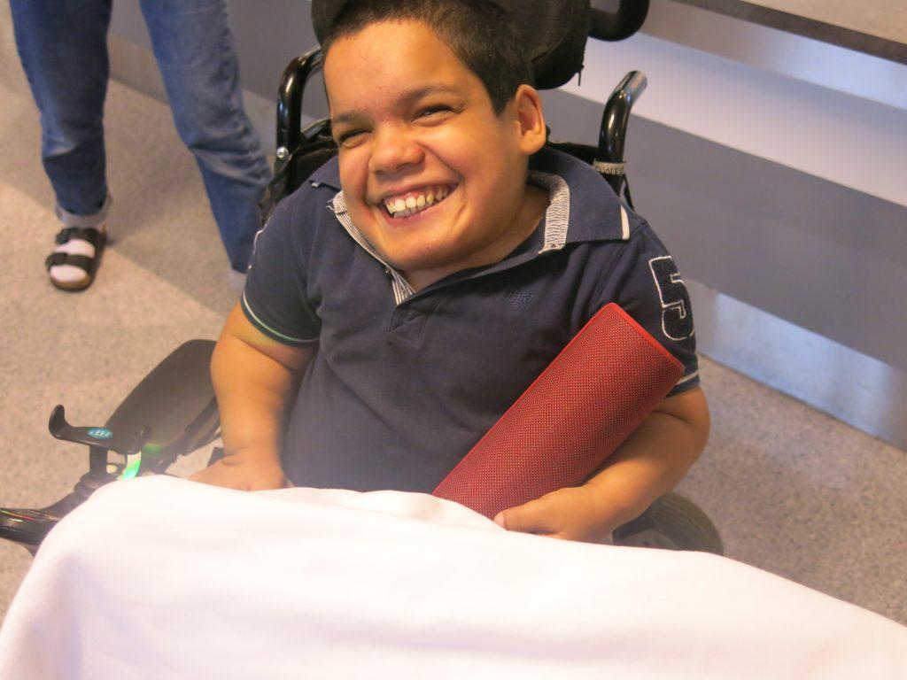 En person sitter og smiler til kamera