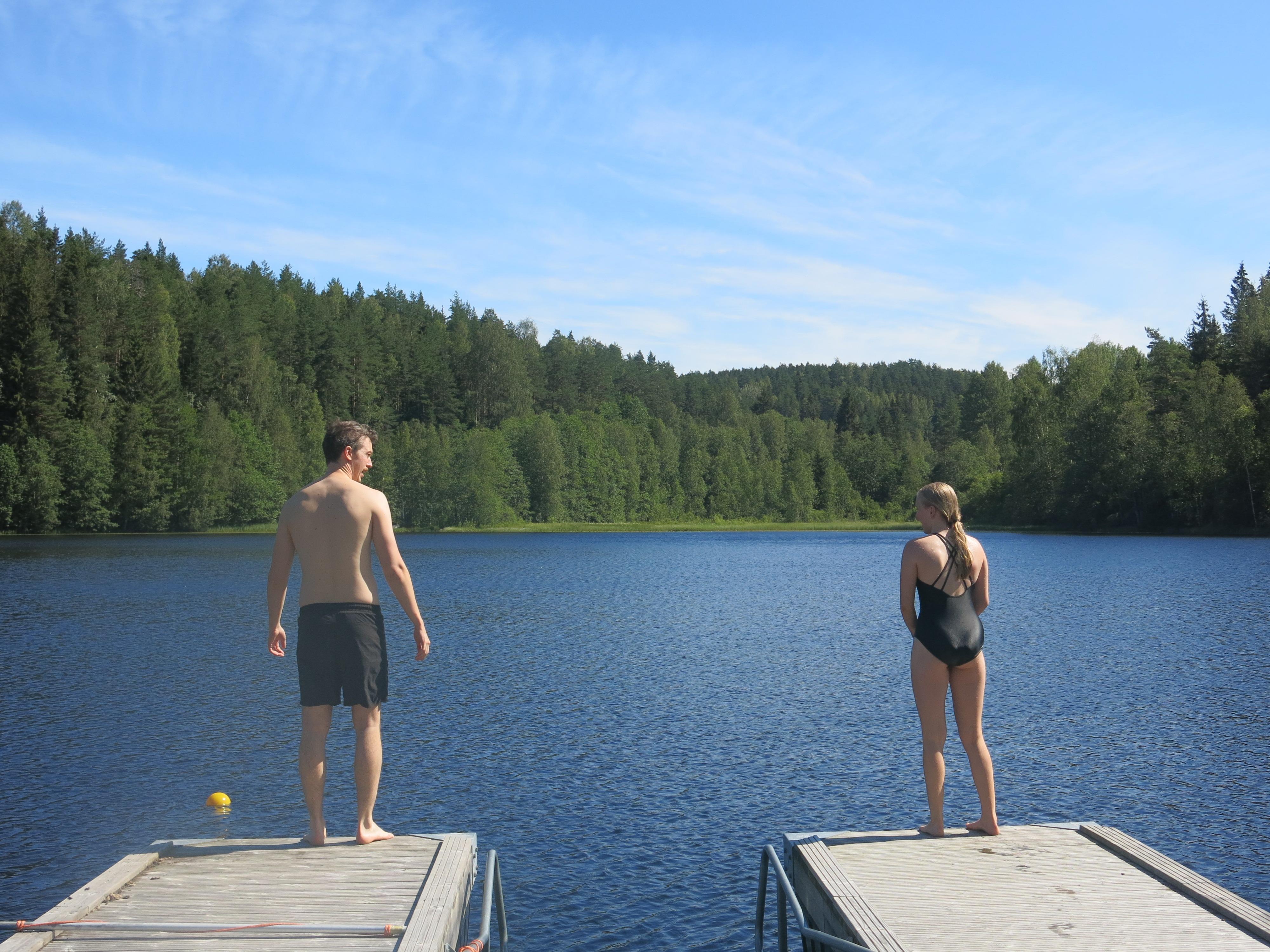 To personer i ferd med å hoppe fra brygga
