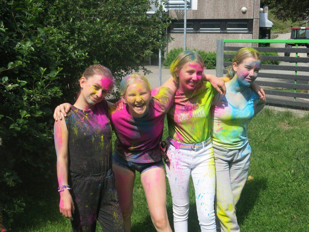 Fire personer dynktet i farger smiler på sletta