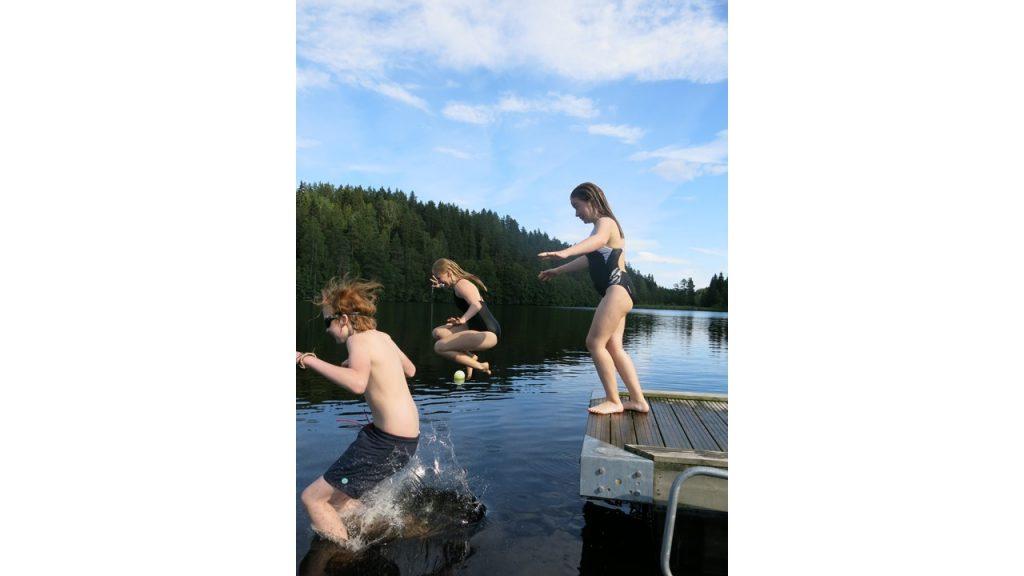 Tre personer hopper i vannet fra brygga