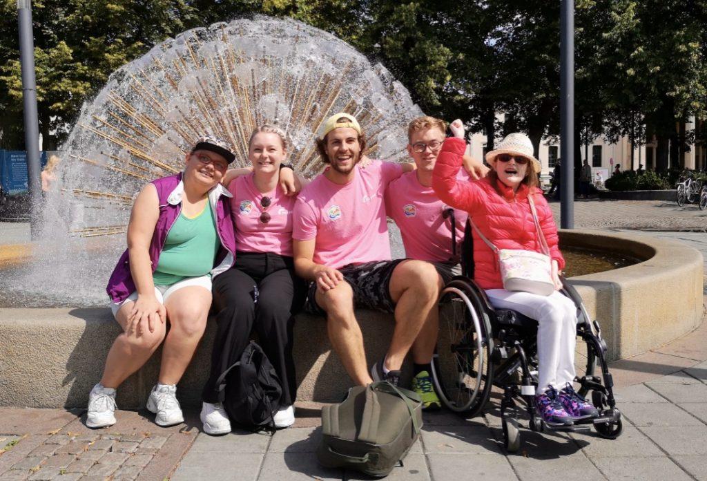 En gruppe poserer foran fontene