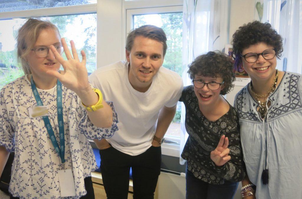 Fire personer smiler til kamera