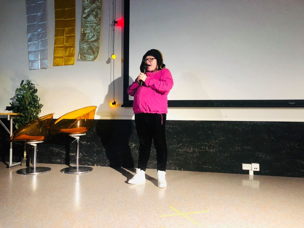 En jente som står på scenen og synger