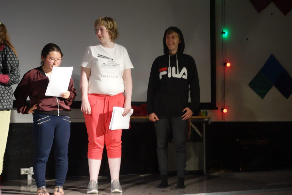 3 personer som står på scenen