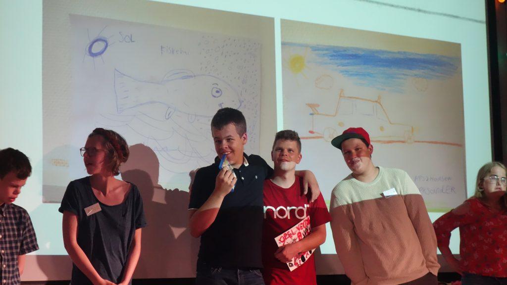 En gruppe personer som viser frem to tegninger