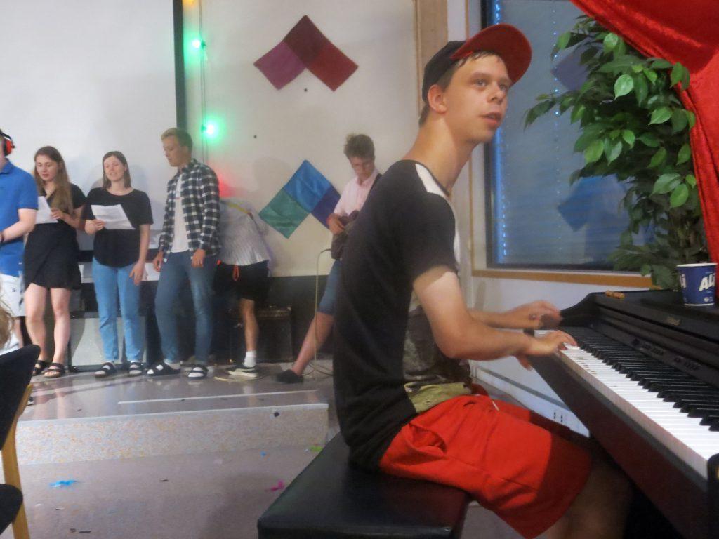 gruppe mennesker som synger og en som spiller piano