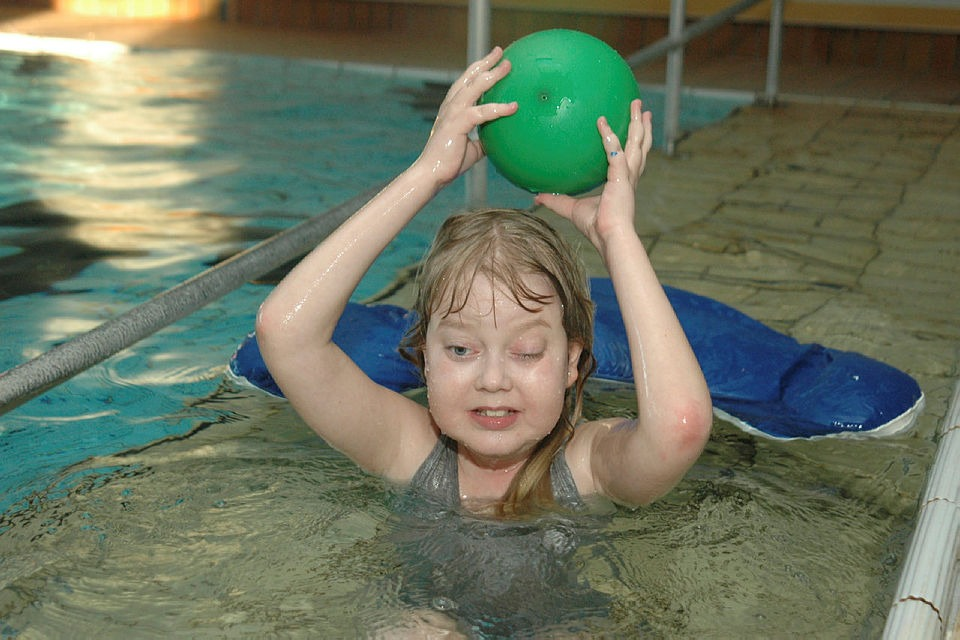 Jente kaster ball i basseng