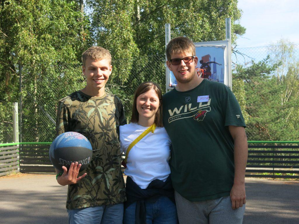 Tre mennesker som står i ballbingen med en ball i hendene.