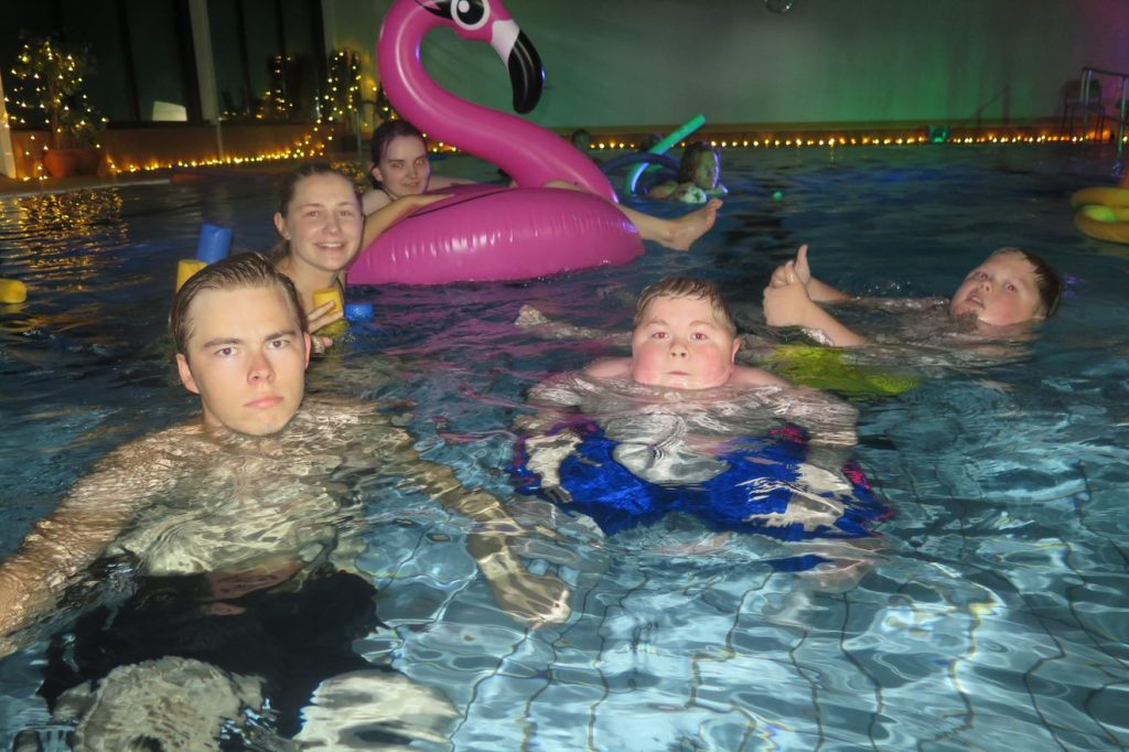 En gruppe mennesker som bader i bassenget