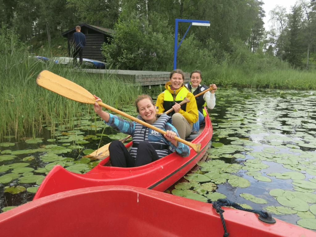 tre mennesker som ror i en kano