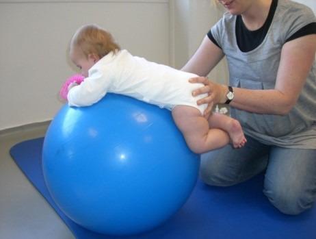 Barn ligger på medisinball