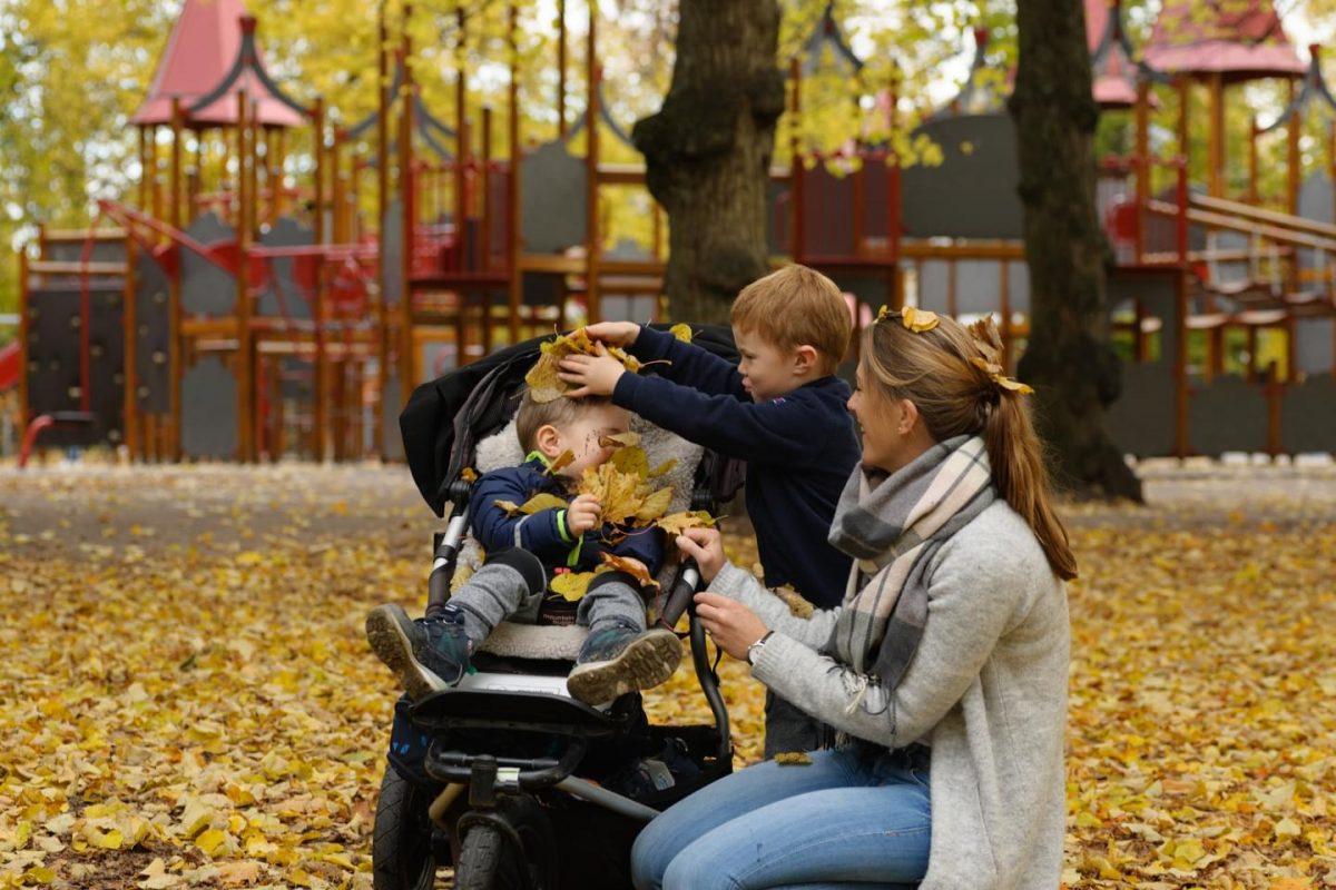 mor og barn på lekeplass med høstløv