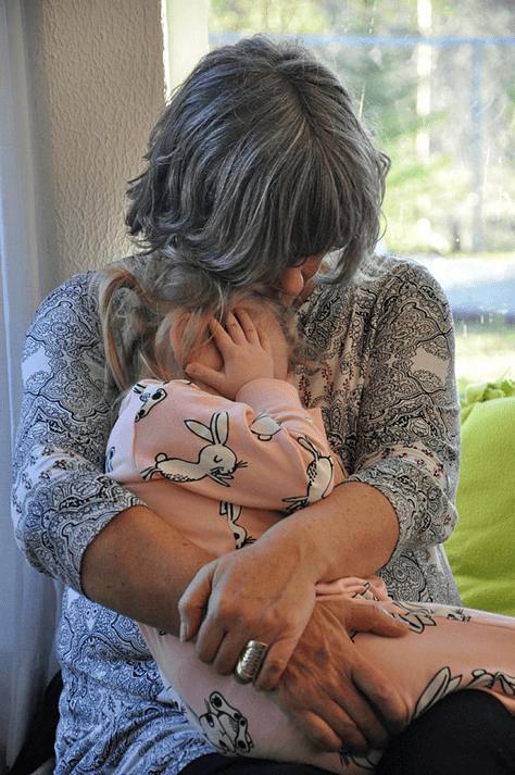 Kvinne som holder rundt barn på fanget