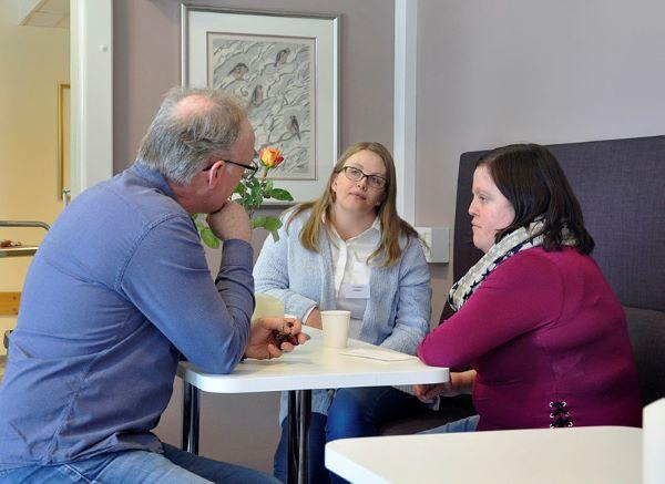 Bildet viser tre voksne personer sitter rundt et bord og snakker sammen