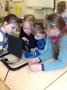 Fire elever ser og peker på skjerm hvor de benytter bilder som kommunikasjon